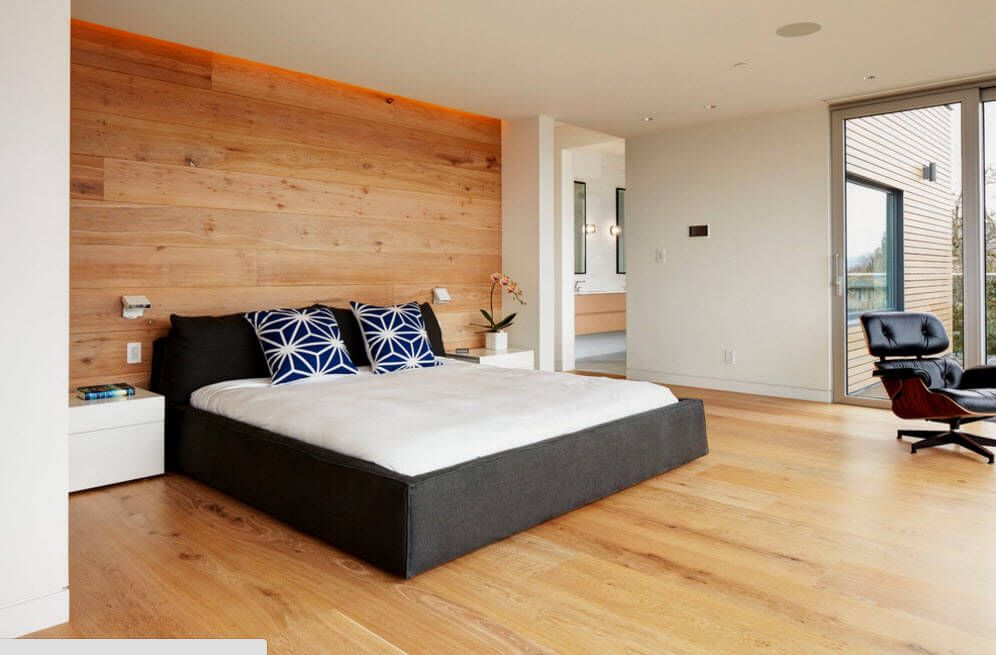 Nice laminate flooring and wooden accent wall for the minimalistic bedroom with dark bed