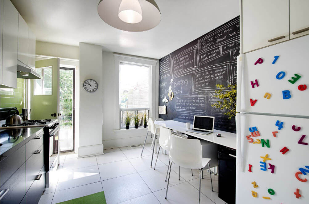 Nice dining zone with white furniture and black wall with chalked messages