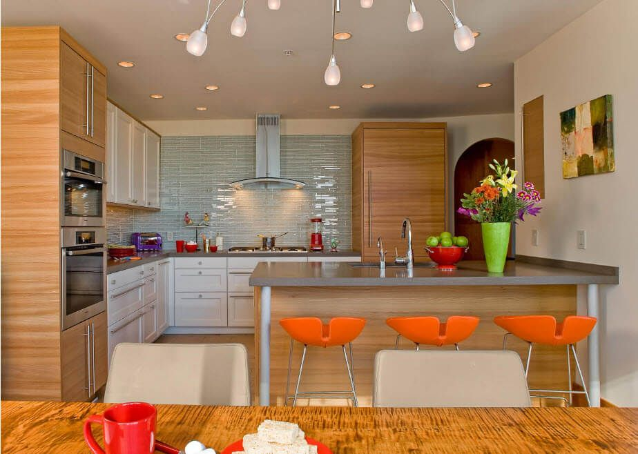 Minimalistic kitchen with joyful orange bar chairs as colorful stains in the design