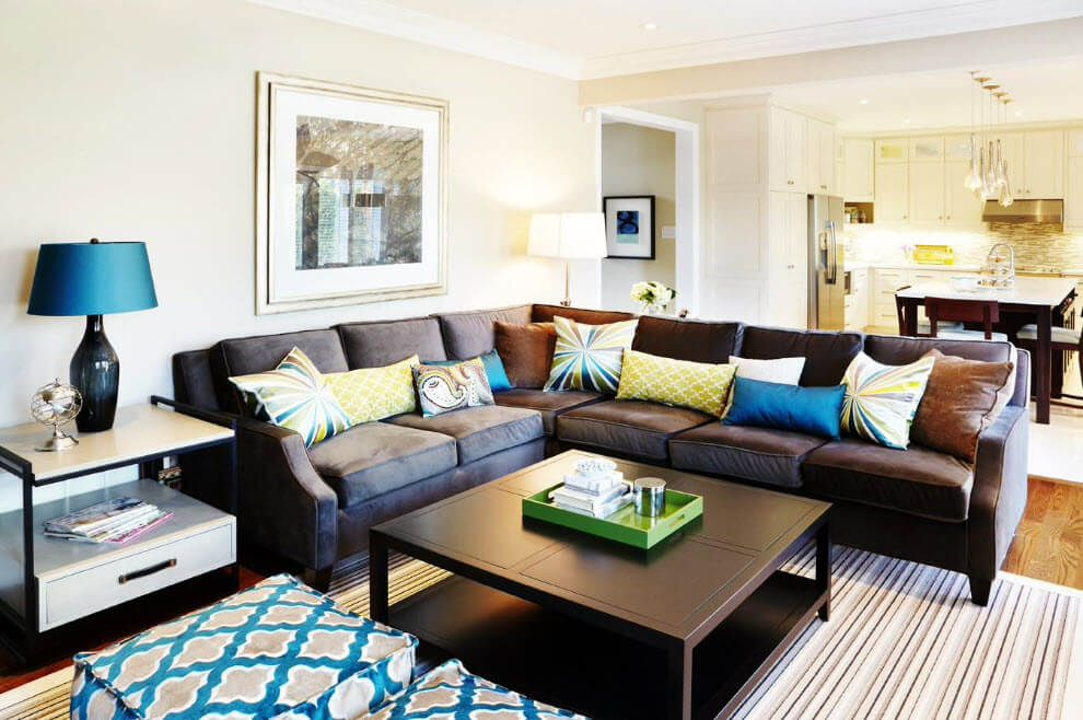 Leather angle sofa and a lot of colorful pillows on it fill the space of the living room