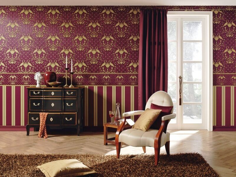 Classic burgundy colored interior horizantally separated by walpaper frieze