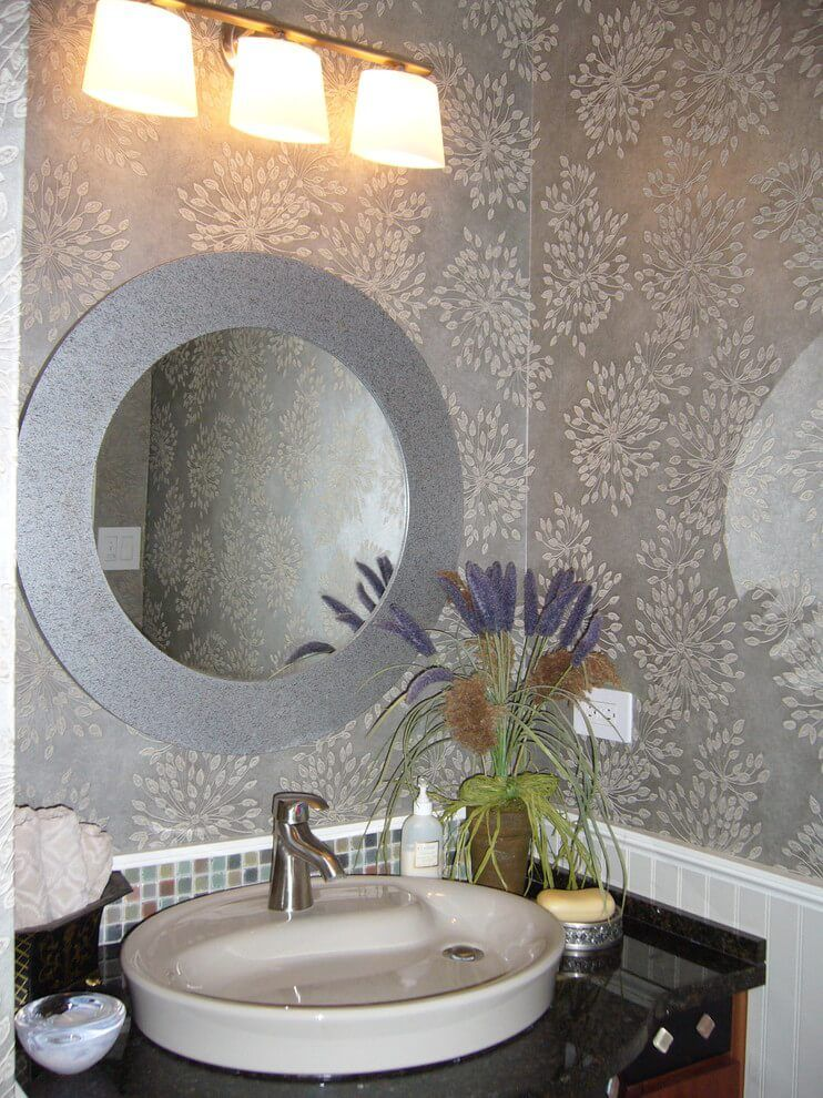 Round mirror in the bathroom and the silver plated wallpaper