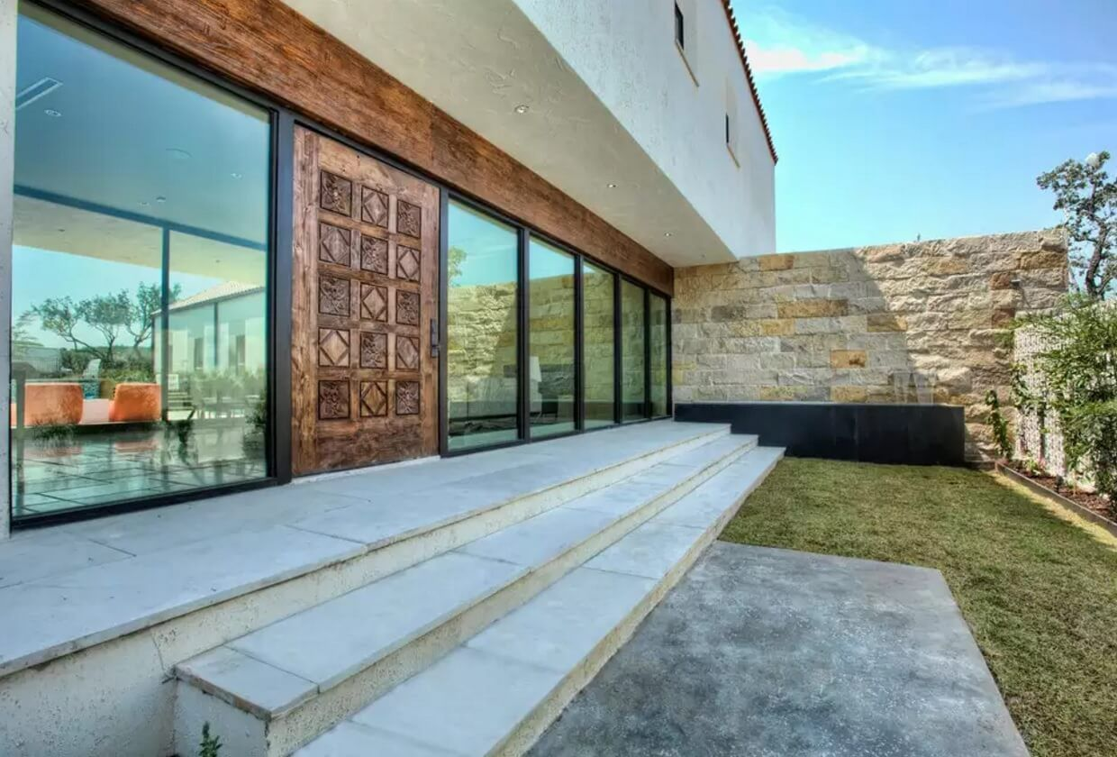 Carved Wooden Doors as Piece of Art in your Interior. Entry door at spectacular monolithic surface of the hi-tech designed private mansion