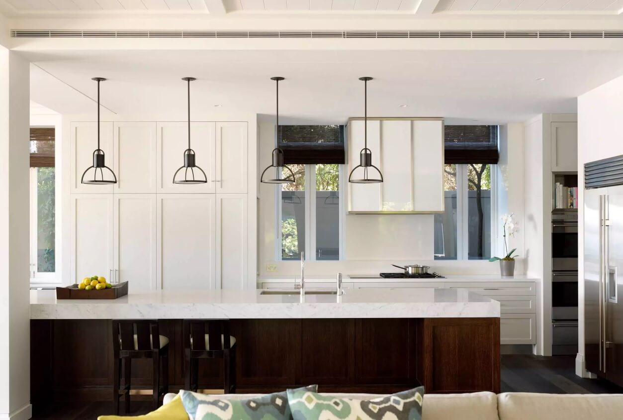 Wrought black shades over the white kitchen island