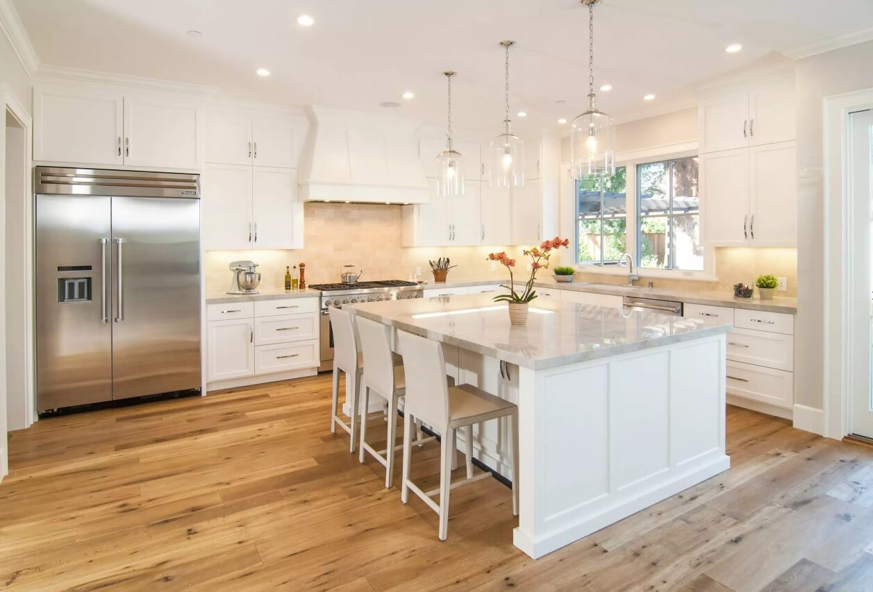 Kitchen Pendant Lighting Possible Design Types with Photos. White large square island in the spacious room with wooden floor