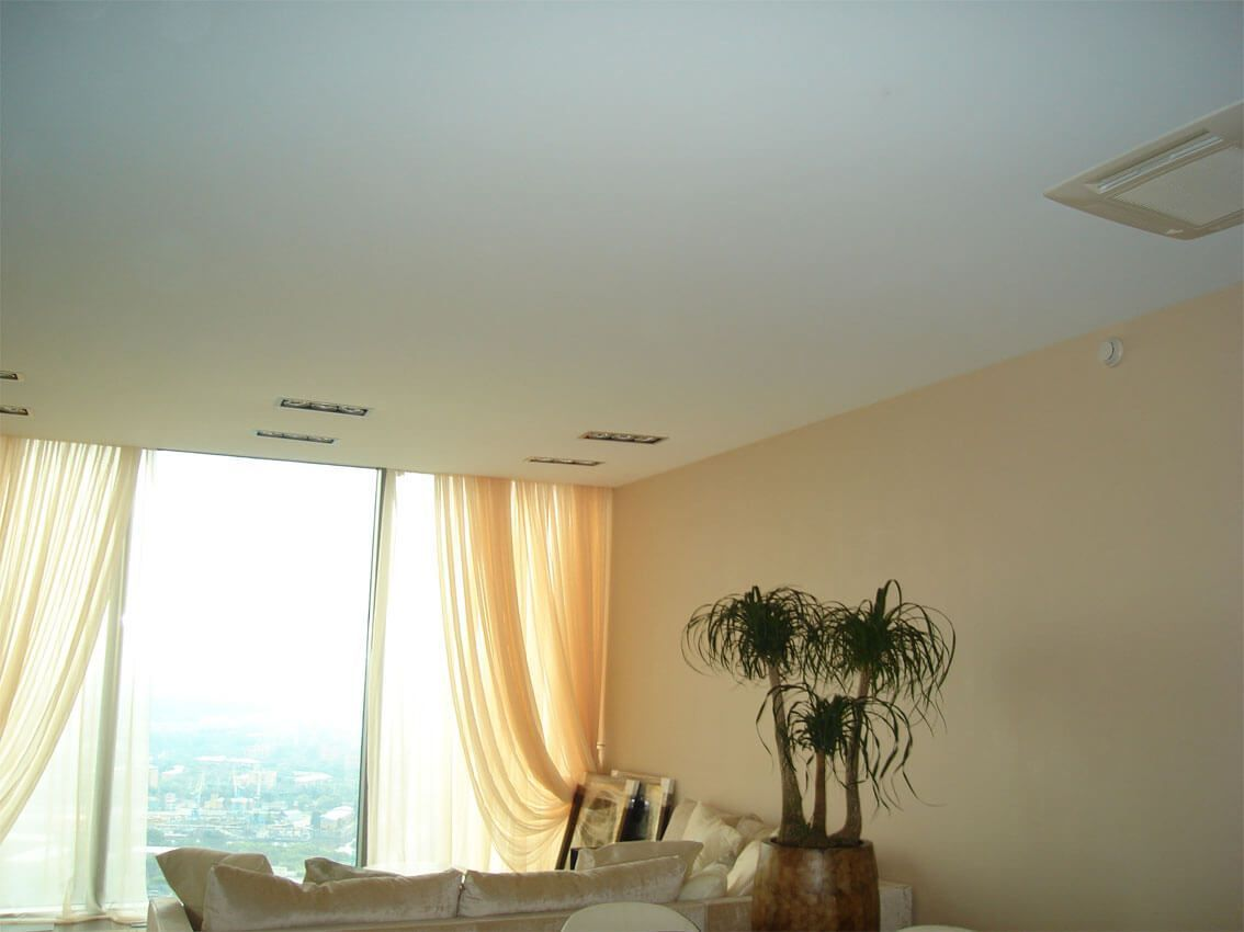 Satin Seamless ceiling in the modern living room with panoramic window and creamy curtains