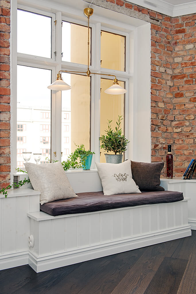 Spectacular brickwork non-finished wall with huge window and the sleeping place with pillows below