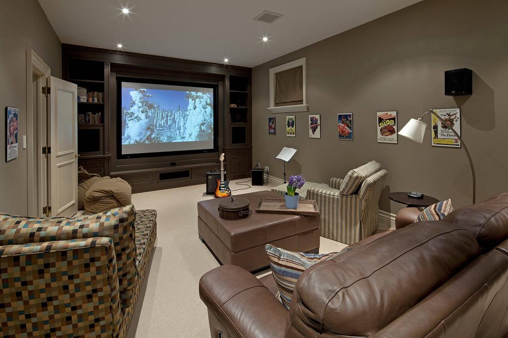 Home Theater as Addition to Large Modern Interior. Chic dark leather couch and leather coated coffe table in the center of the area