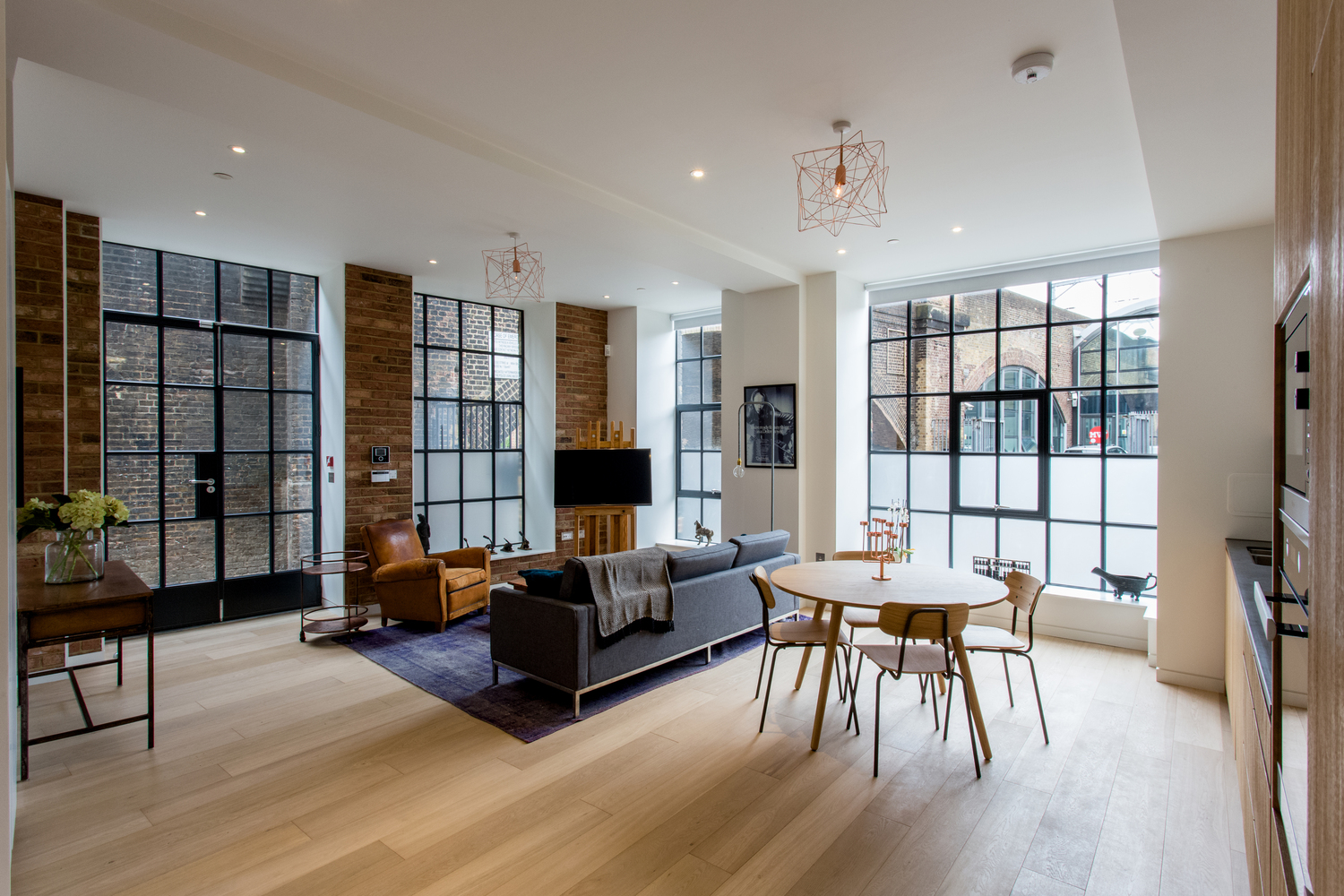 Zoning Living Room's Multiple Functional Areas with Decor and Lighting. Large studio in modern minimalistic style with elements of industrial style