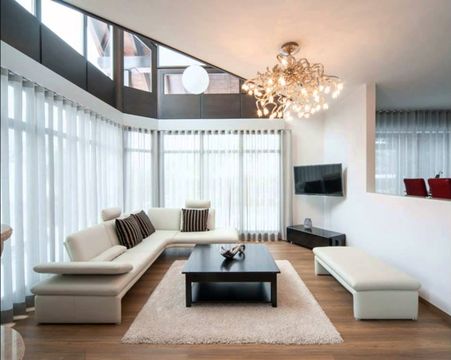 Zoning Living Room's Multiple Functional Areas with Decor and Lighting. Huge space in light colors with black coffe table on a fluffy rug