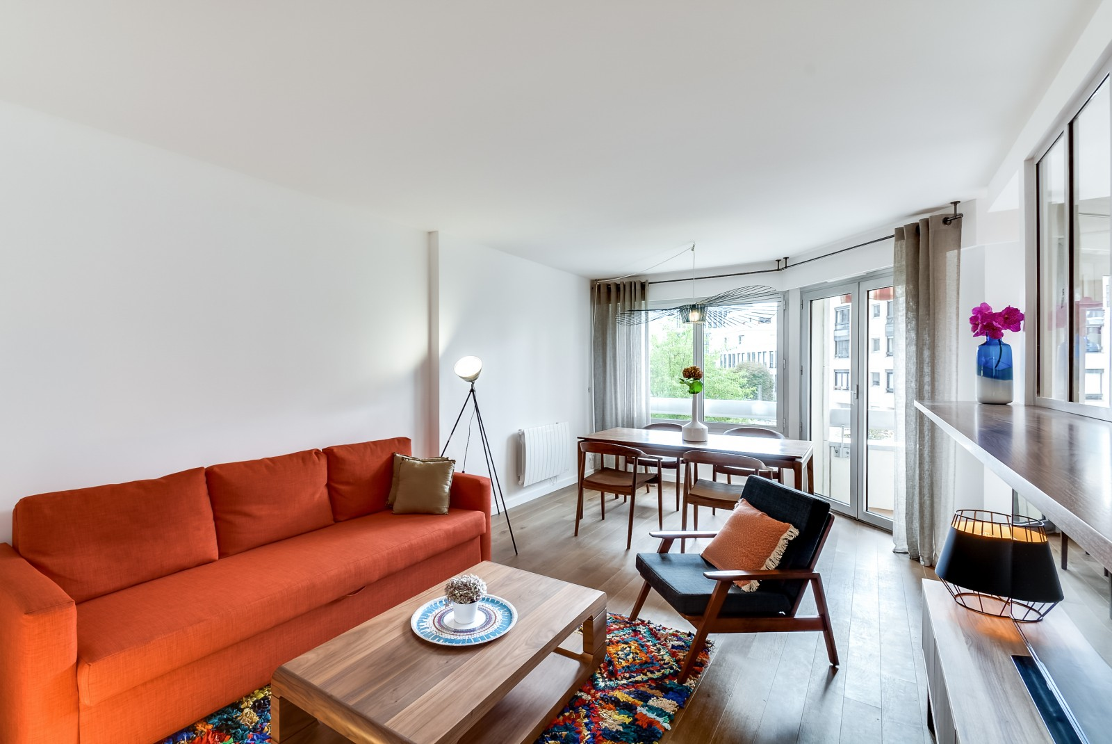Zoning Living Room's Multiple Functional Areas with Decor and Lighting. Bright spot of the orange sofa in the gresh an dlight modern area