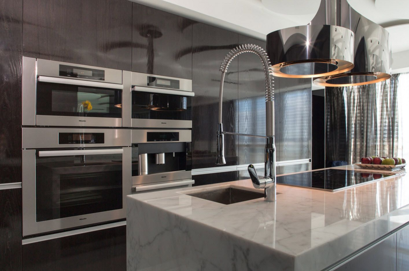 Rounded big steel tap in the modern kitchen interior with marble countertop
