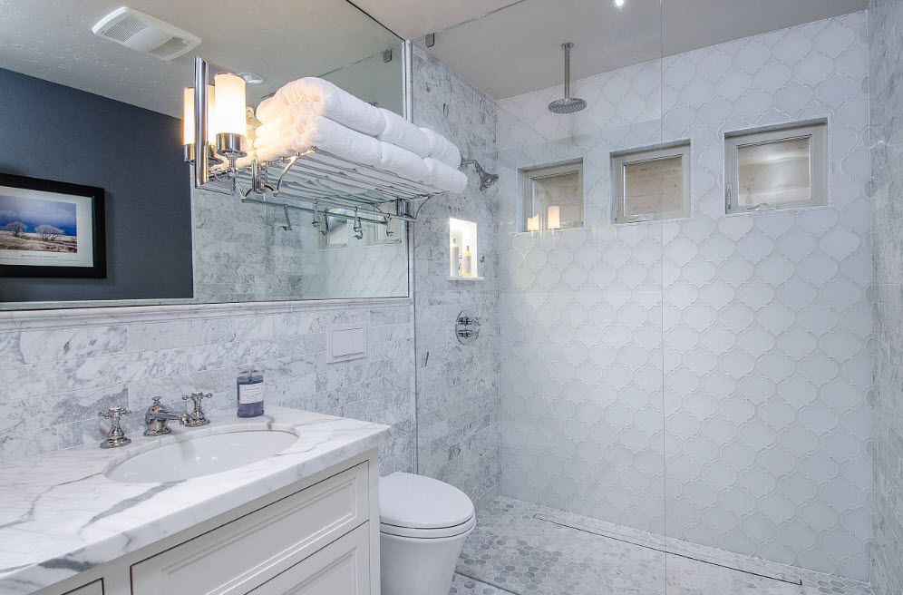 Nice sterile white interior of the modern bathroom with small tile and stone imitating surfaces