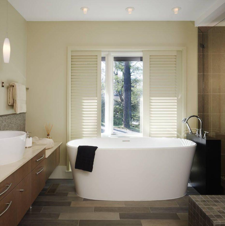 Light creamy bathroom design and white oval bathtub