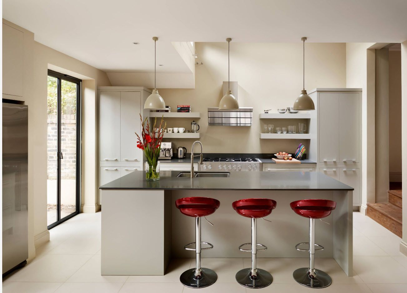 Red seats of bar chairs and steel legs at the glass countertop of the kitchen island