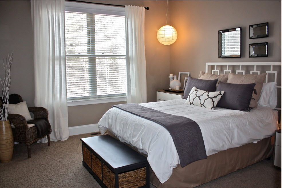 Gray bedroom with bulb looking glass lampshade above the bed