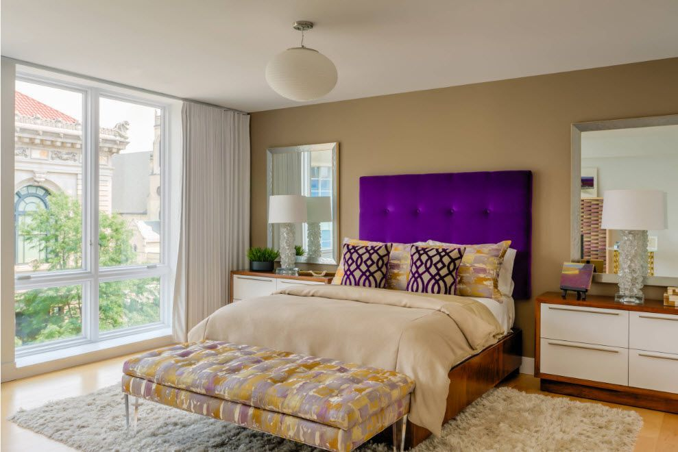 Sandy interior theme of the bedroom with bright contrasting violet uholstered headboard