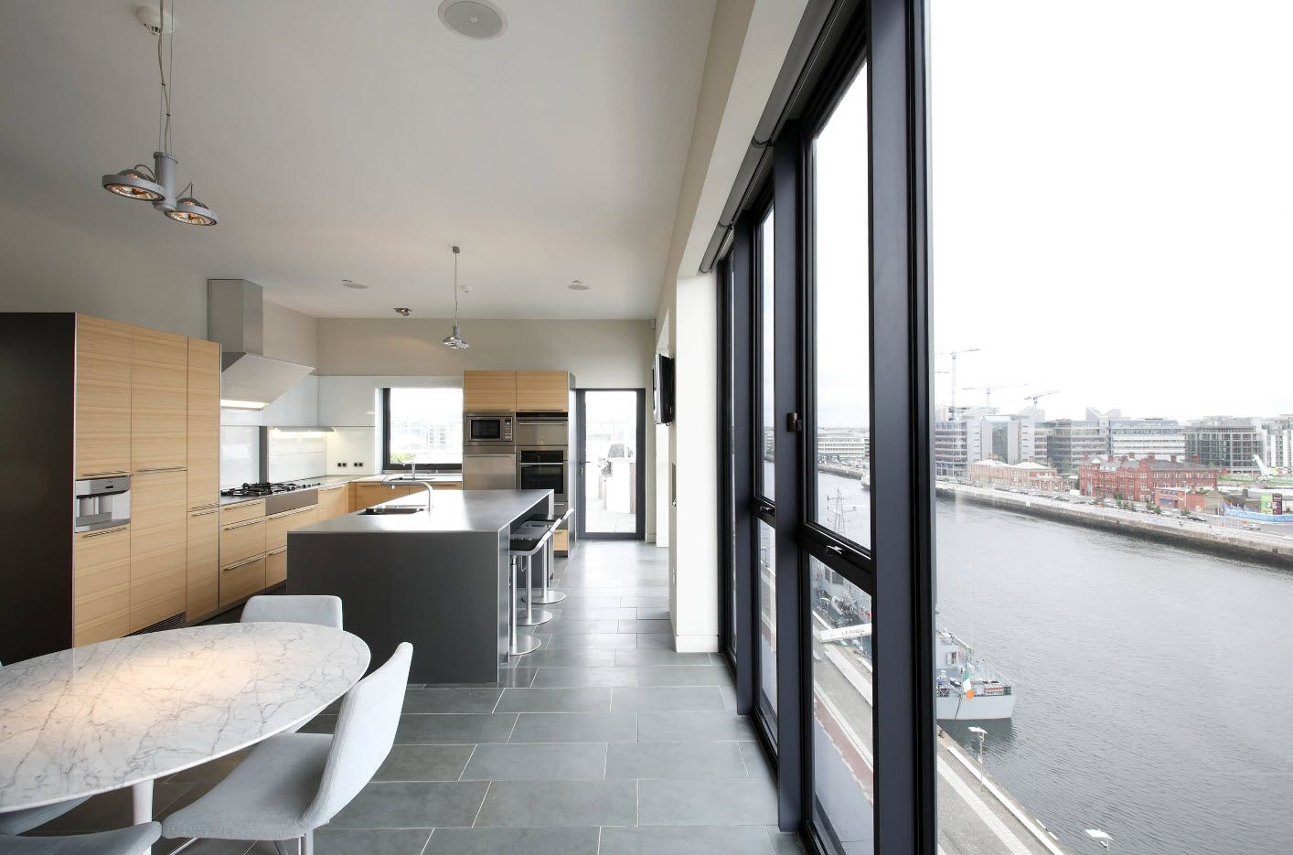 Urban apartment design with large window oanes and gray kitchen island as a accentual pedestal in the center