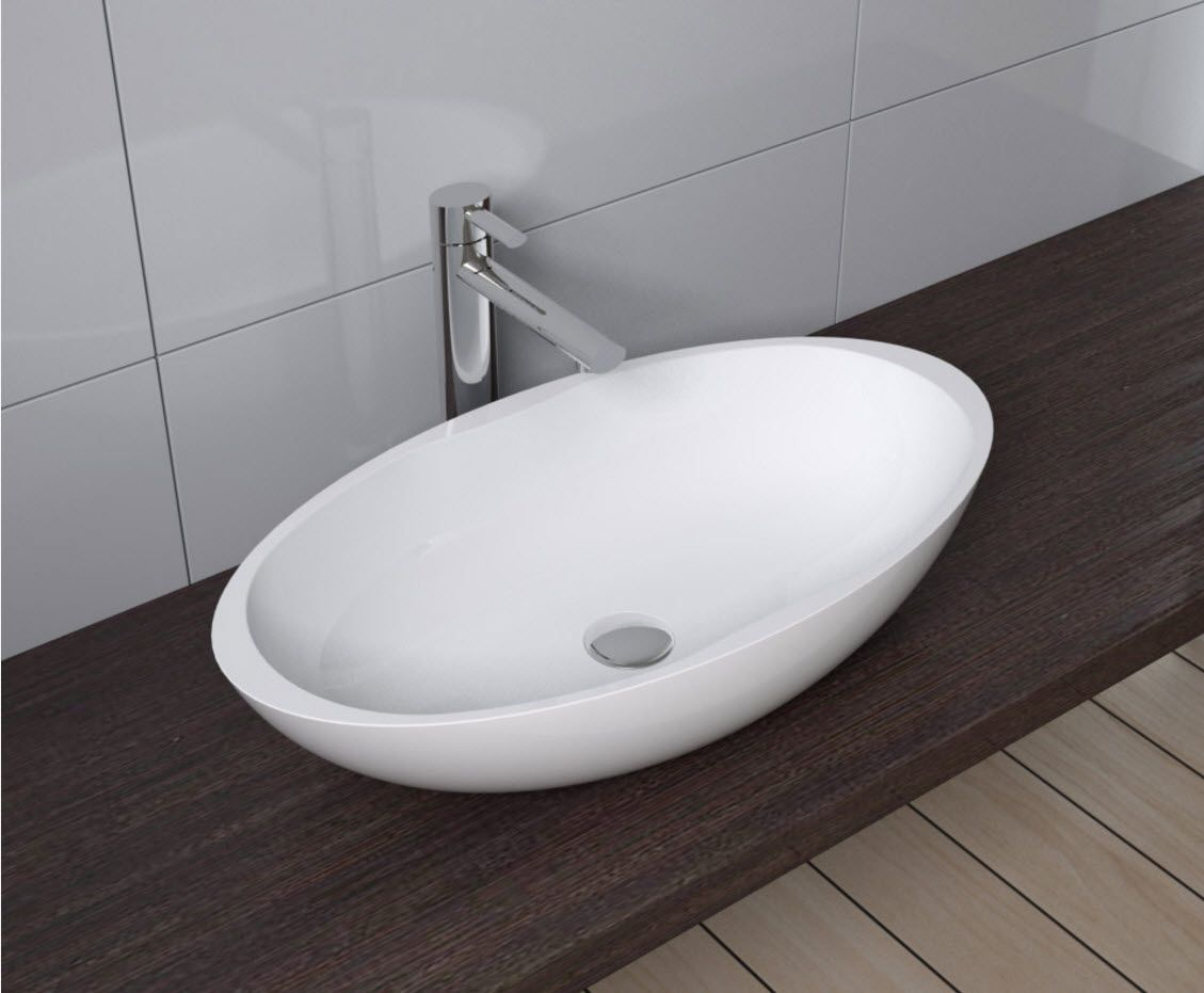 Oval sink for the modern bathroom on the dark wooden vanity