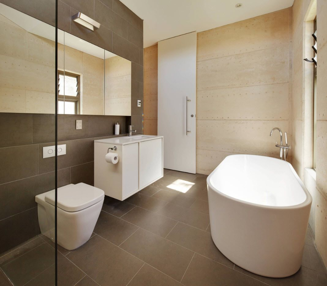 Gray floor tile and wall finish and the bathroom full of suspended plumbing