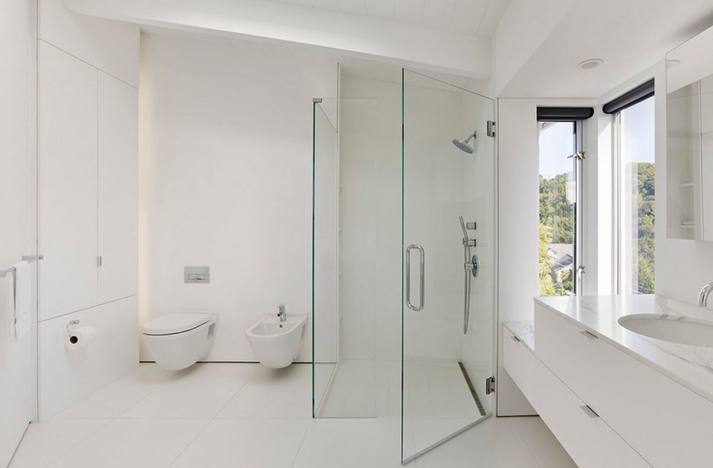 Totally white minimalistic bathroom design with glass shower cabin