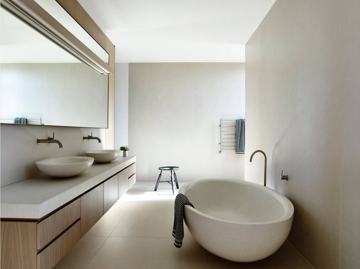 White natural lit bathroom with black taps and wooden surfaces' contrast