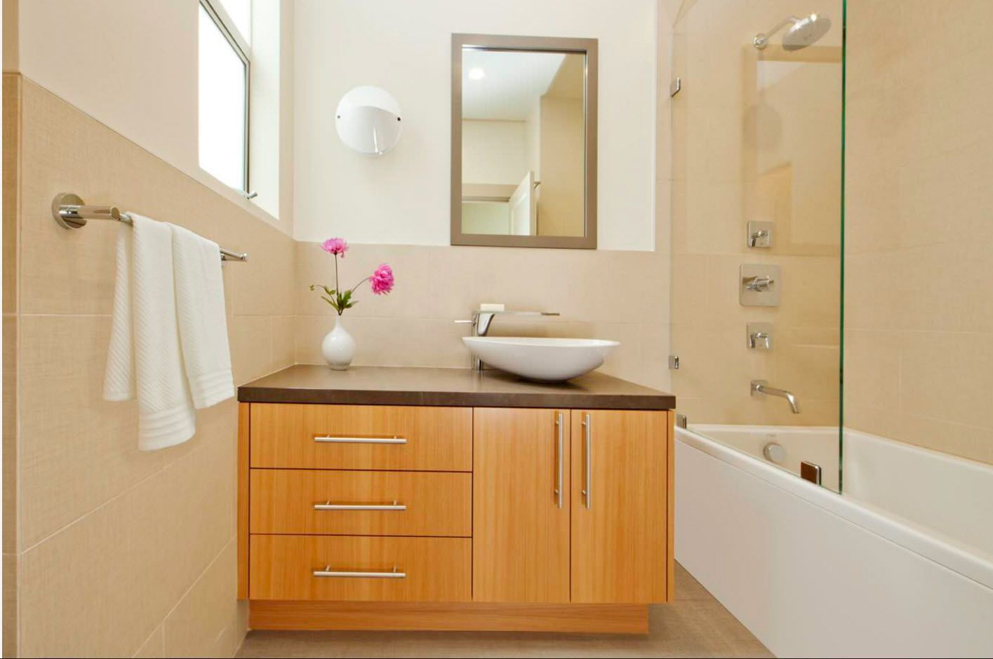 Neat bathroom vanity with light wooden surface