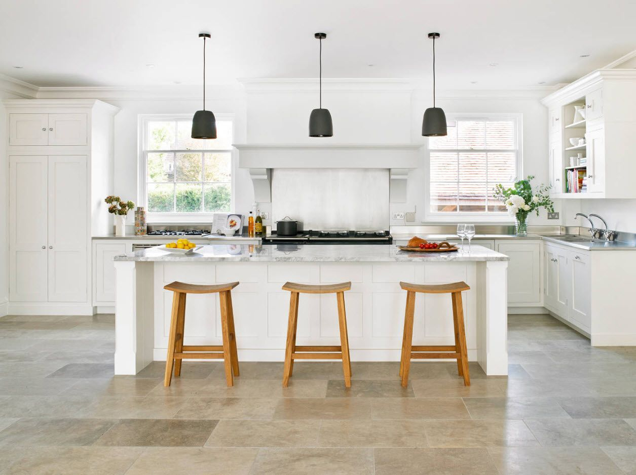 Wooden stools and white table crowned by dark gray lampshades