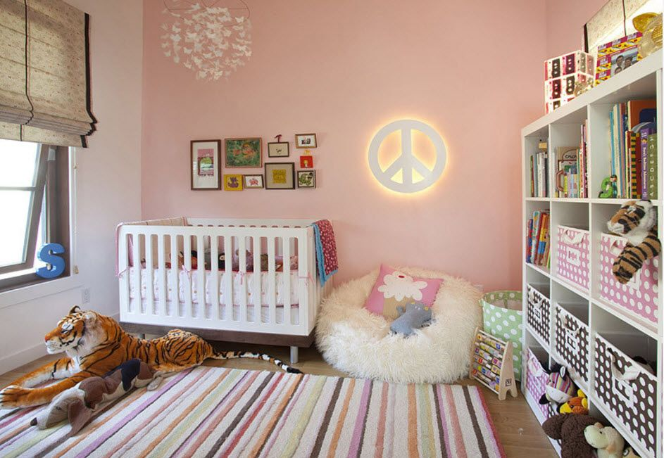 Nice pinky wall decoration in the children's room with crib and backlighted wall elements