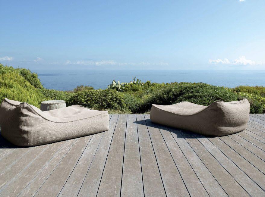 Frameless upholstered sunbeds at the wooden terrace