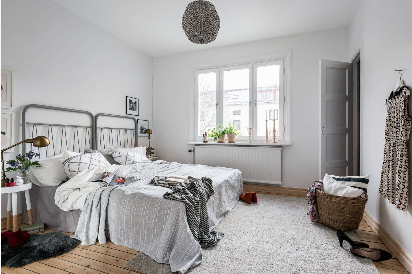 Absolutely white ascetic bedroom atmosphere with metal headboards of the beds