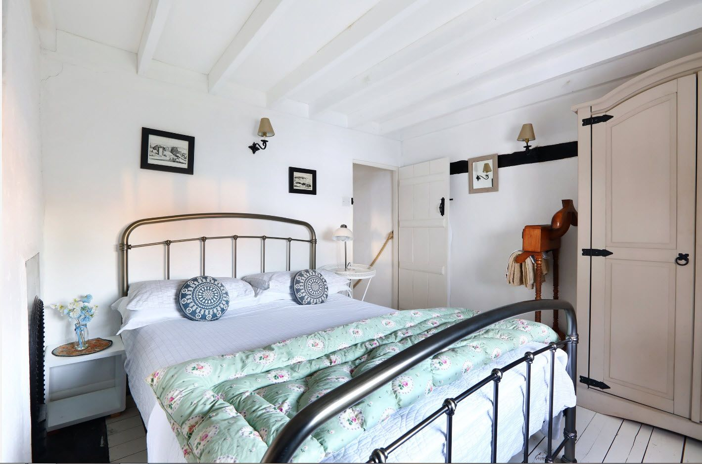 White ceiling beams and metal sides of th bed