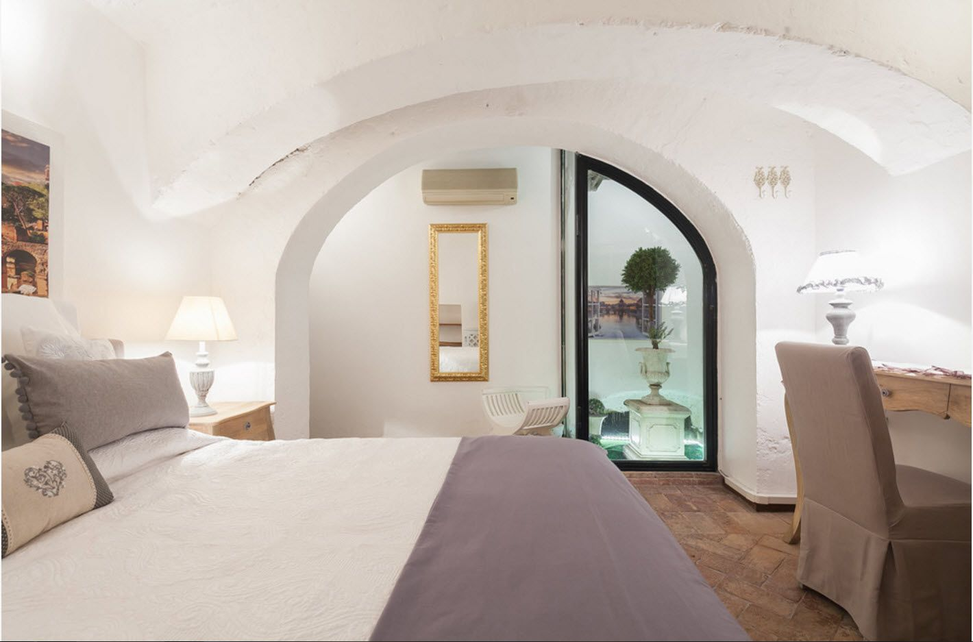 White bedroom with arch to the bathroom