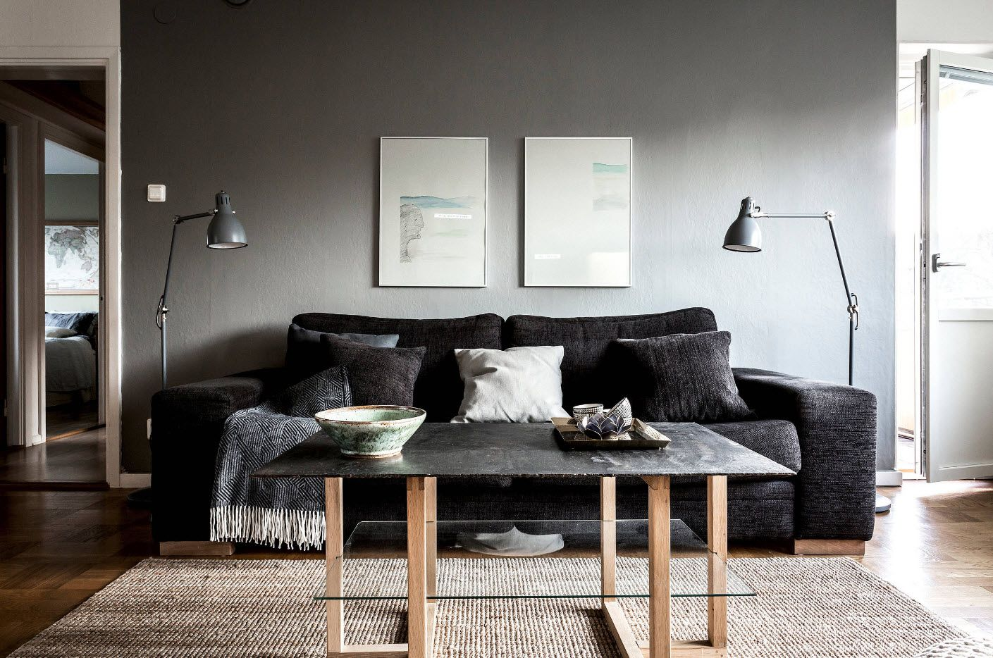Dark gray wall with pictures and black sofa with lamps and glass coffee table at the front