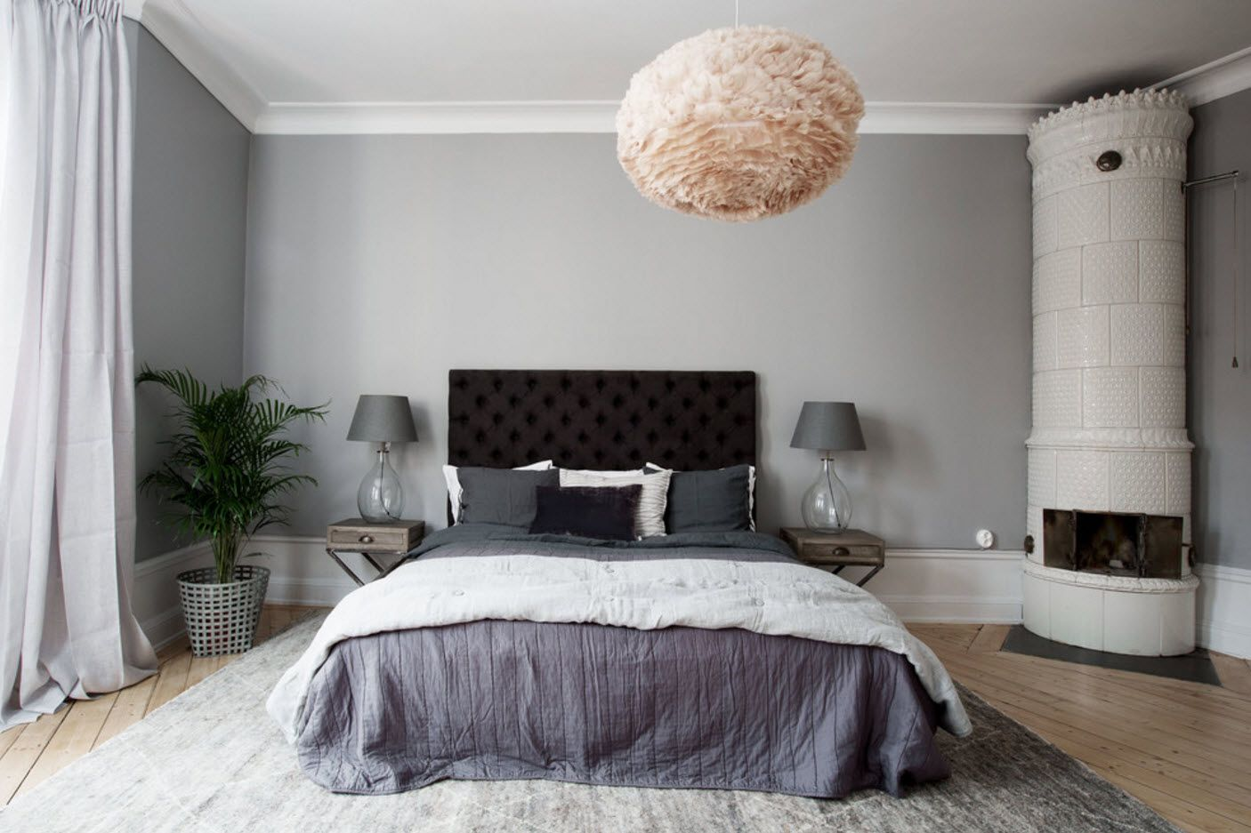 Classic bedroom interior with quilted dark headboard and platform bed