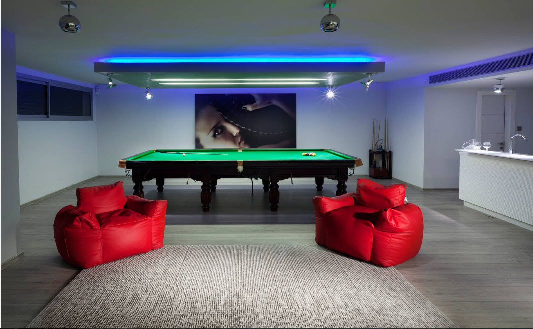 Billiard room with red frameless armchairs