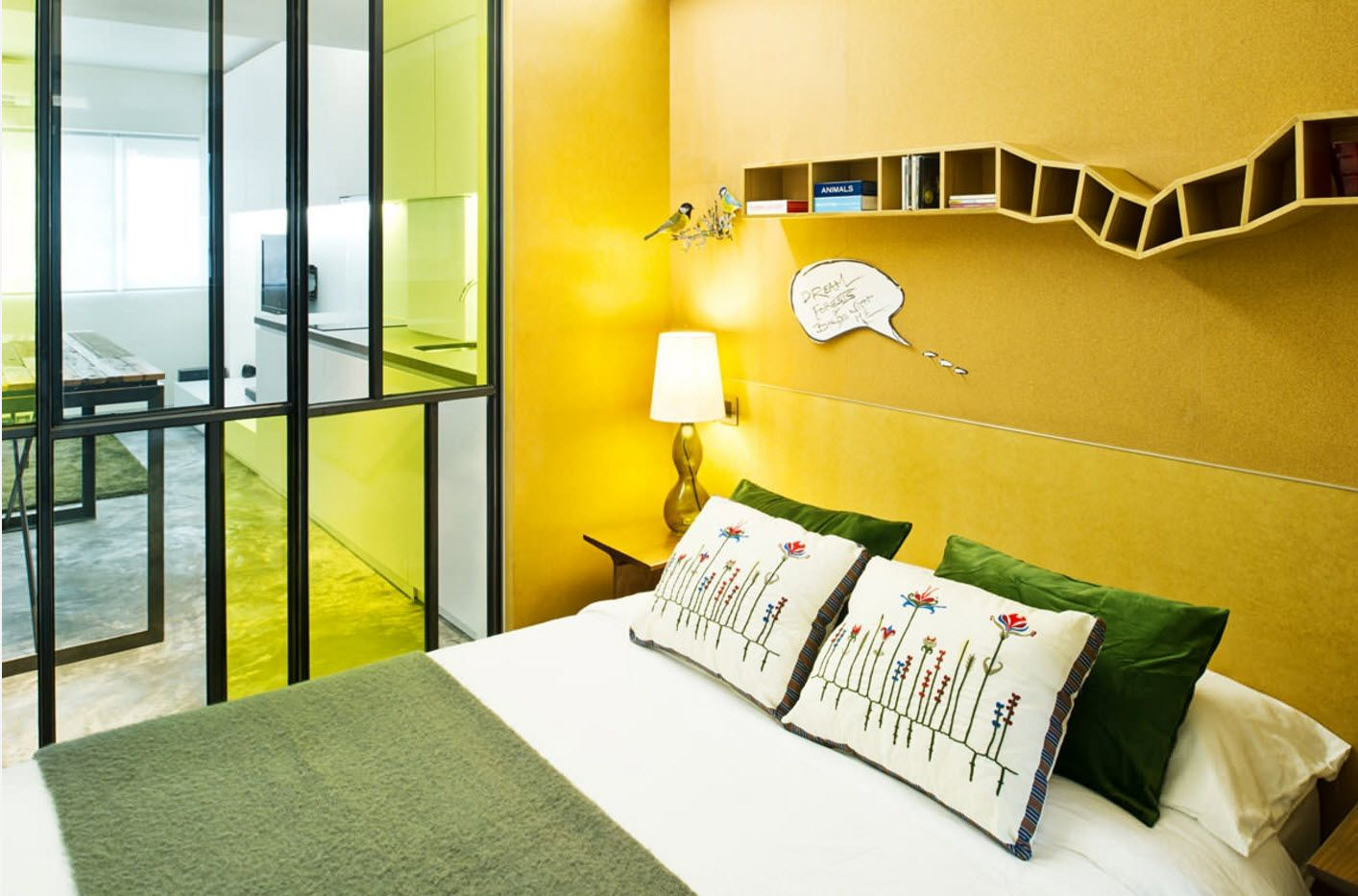 Yellow walls and the glass surfaces all-round the bed