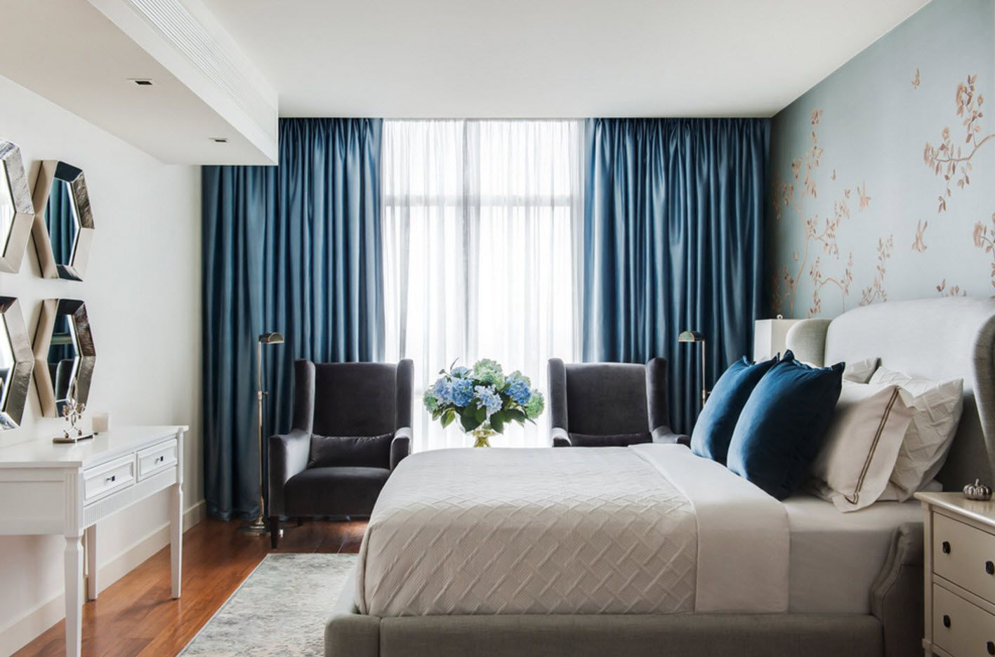 Spectacular silk blue draperies with hiddfen carnice; platform bed and с couple of armchairs
