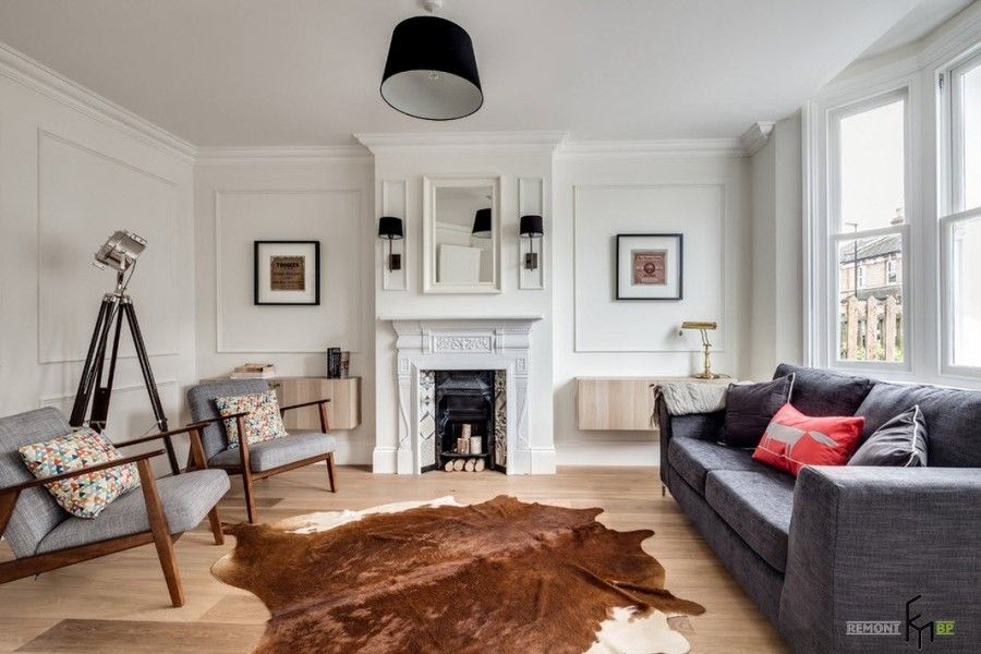 Primordiality and putiness of the impeccable white English country style interior design with cow's pelt in the middle of the large living room