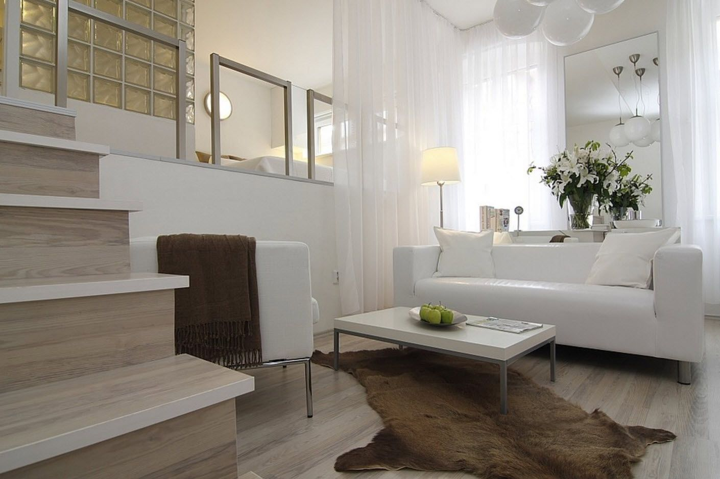 Multilevel studio apartment with living room and open layout of bedroom finished in restrained Modern and Scandi styles