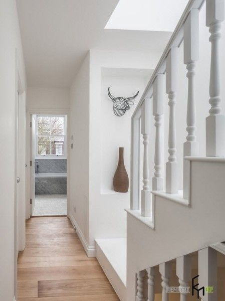 Modern English Country Style Interior Design Example. Small narrow hall with white staircase