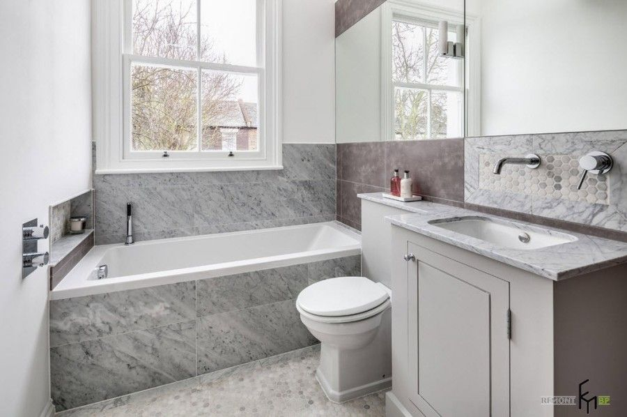 Modern English Country Style Interior Design Example. Marble trimmed bathtub in the large bathroom with toilet and sink