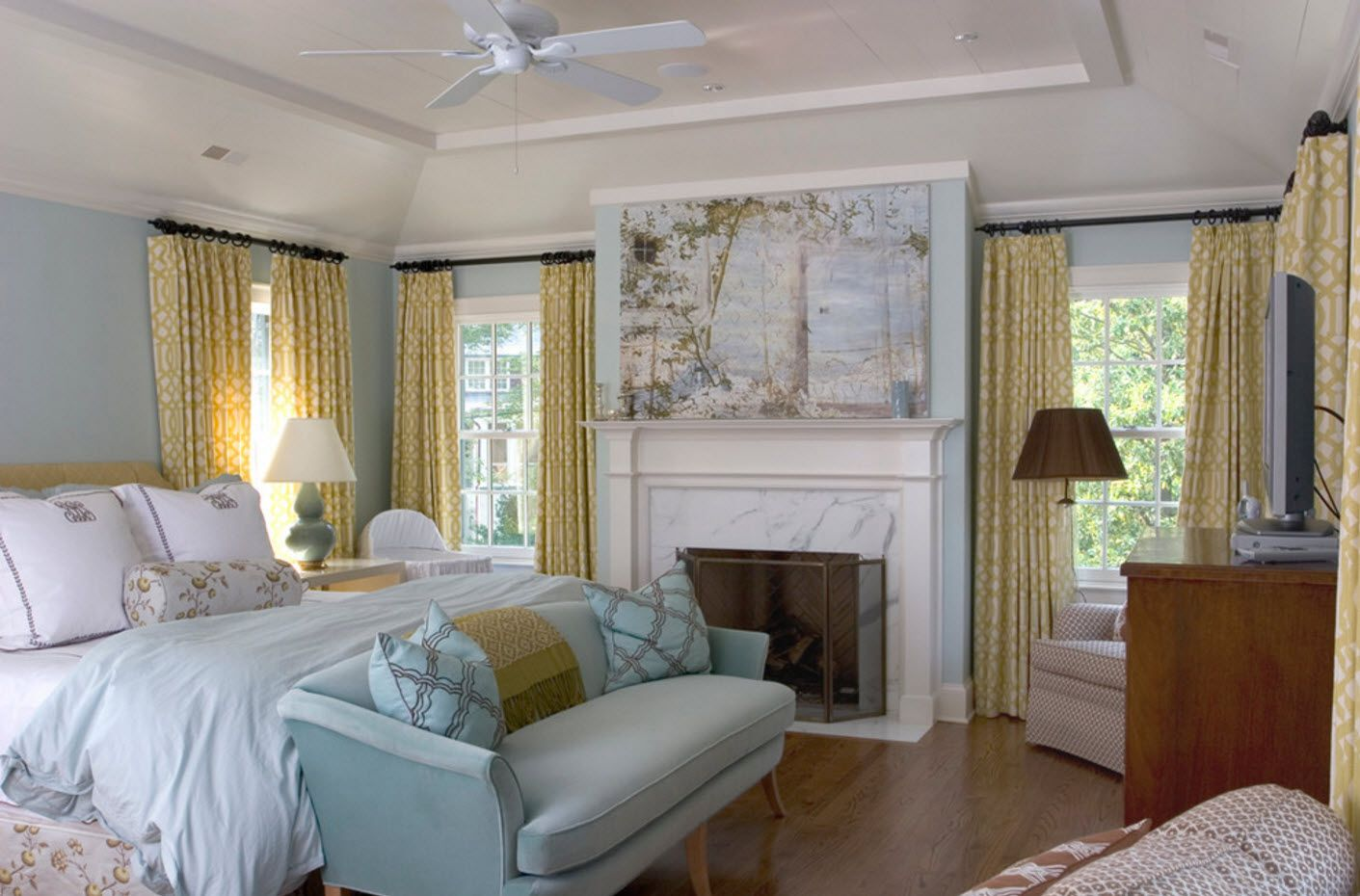 Yellow drapes as an accent in the classic styled light blue colored living room with the hearth