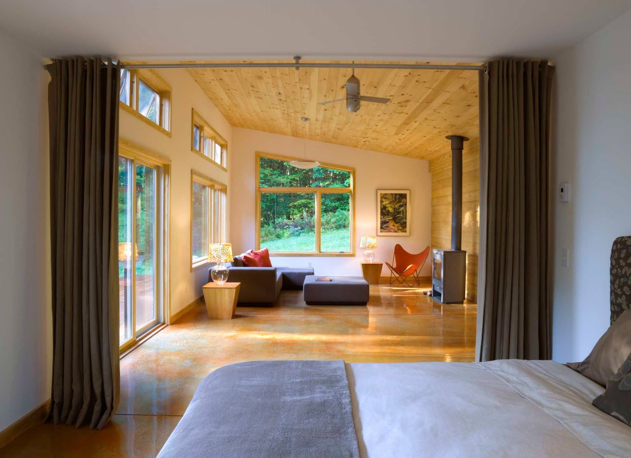 Open layout of the bedroom in the private house with slanted ceiling and wooden trim of it
