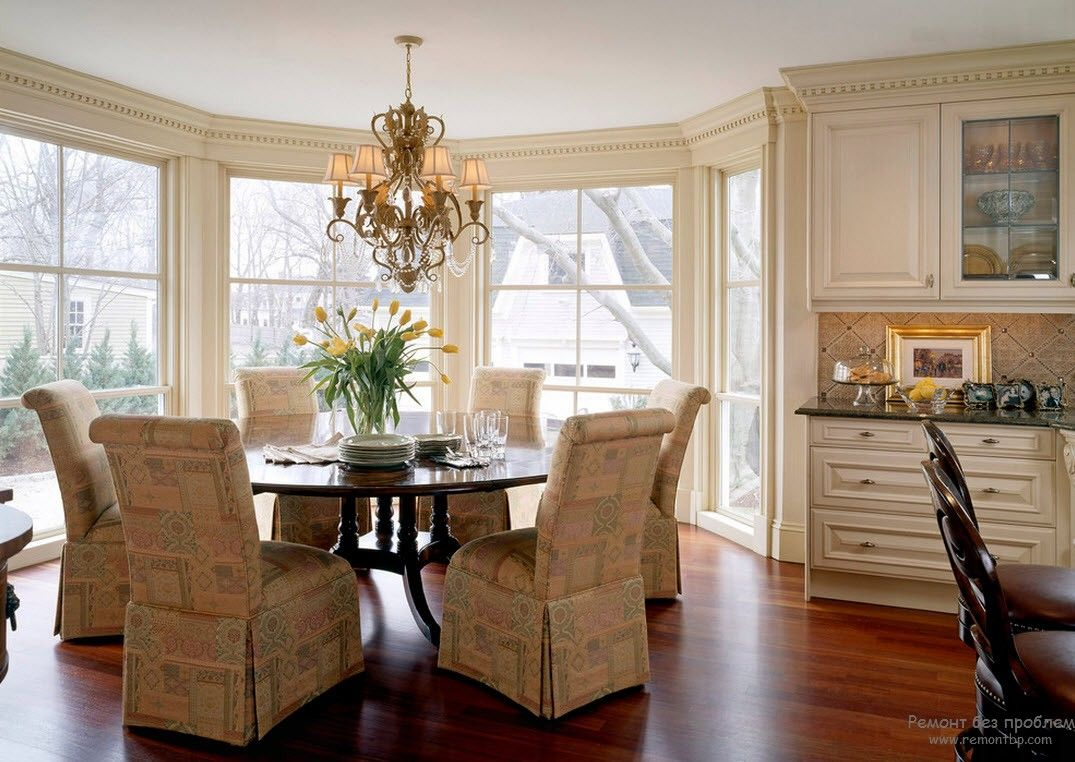 Spacious first floor living room with bay window and dinner group of upholstered armchairs