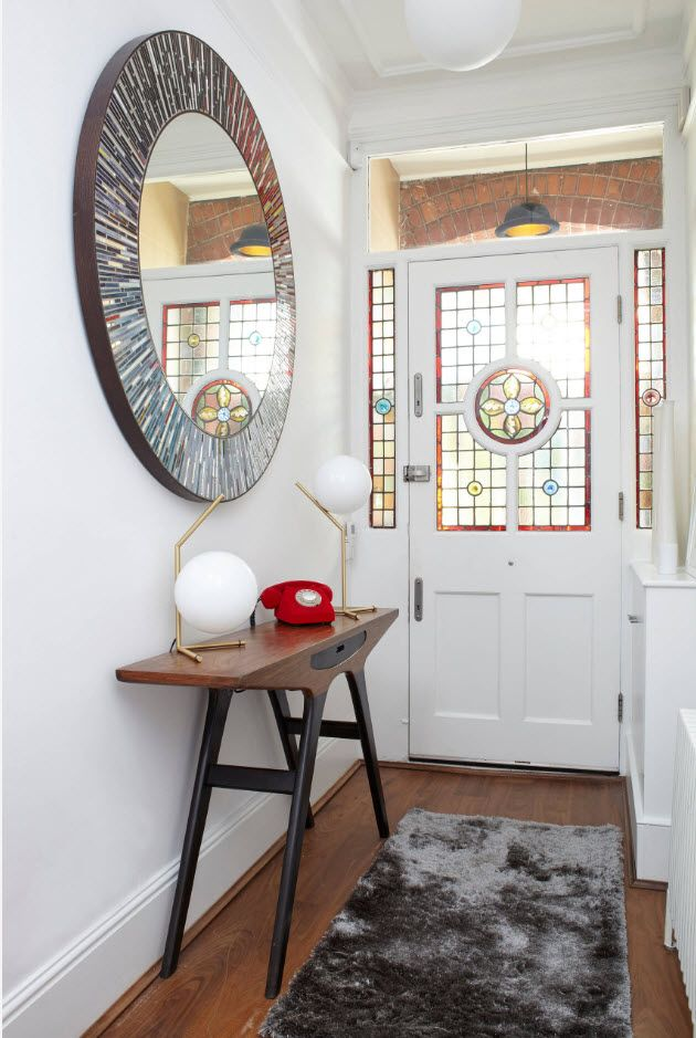 Large round mirror and white set in the hallway