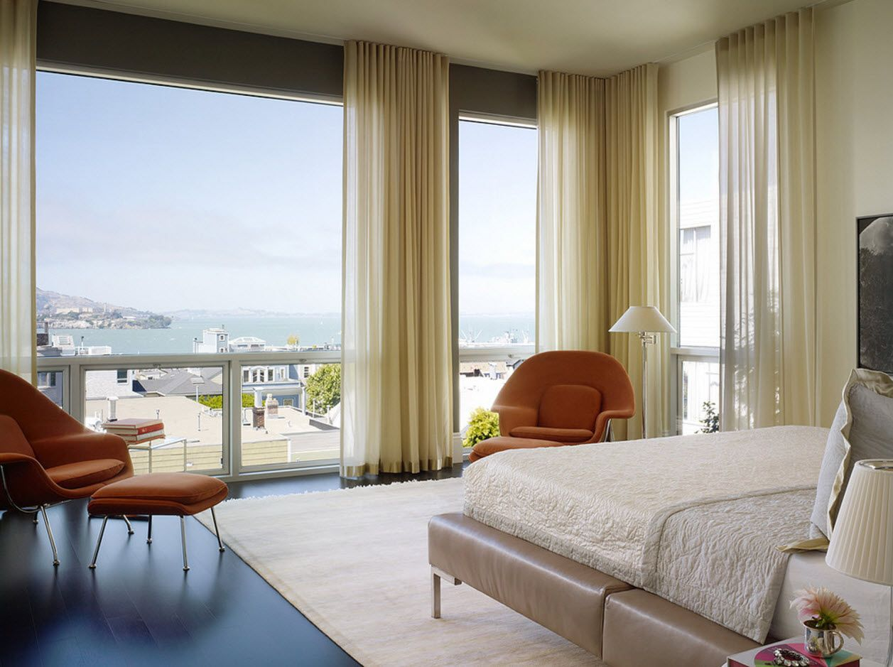 Screen panoramic windows at the seaside apartment and with creamy curtains