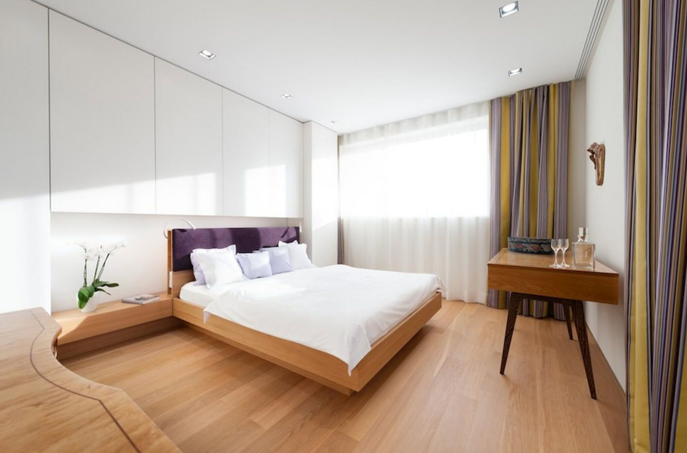 Spectacular design of the modern boxed bedroom with wooden flooring, platform bed and glossy plastic glossy headboard