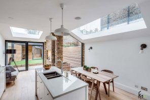 Modern English Country Style Interior Design Example. Kitchen island and the dining zone with panoramic skylight