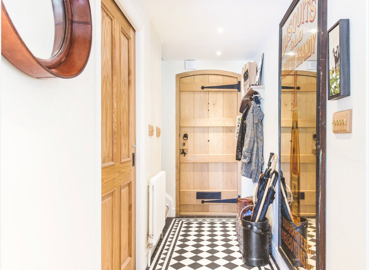 Innovative but nevertheless rustic design style for the modern hallway with wooden doors and chess flooring